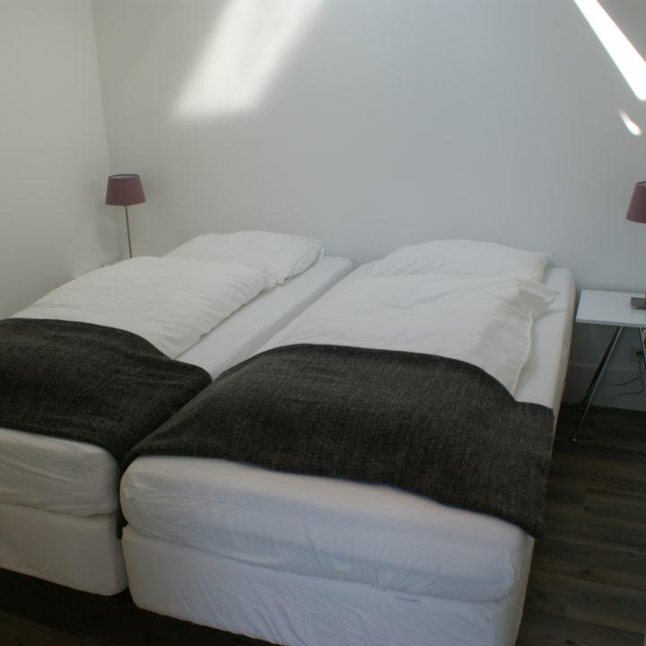 Tweepersoons slaapkamer met opgemaakte bedden