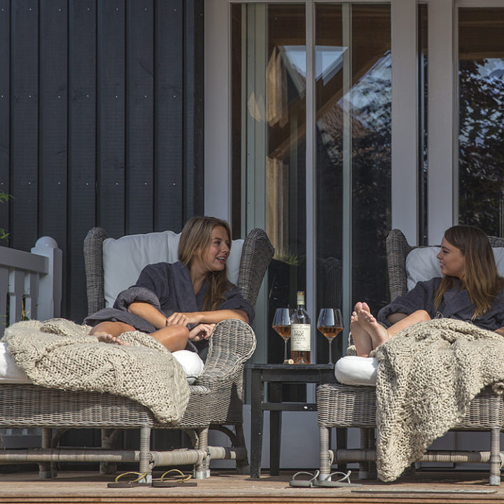 Twee dames genieten op loungebedden van hun tijd in de wellness van het hotel