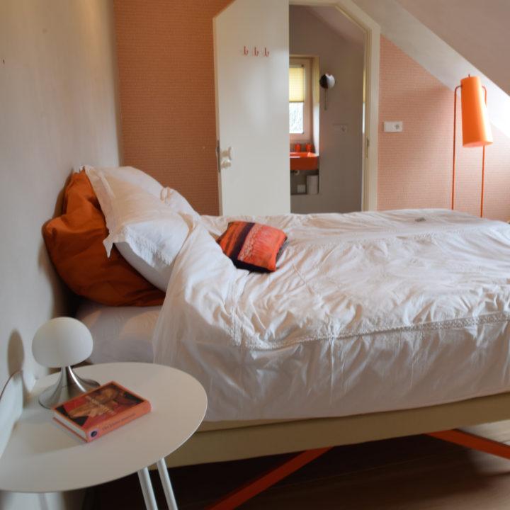 Kamer Oranje Boven met een heerlijk bed en oranje accenten