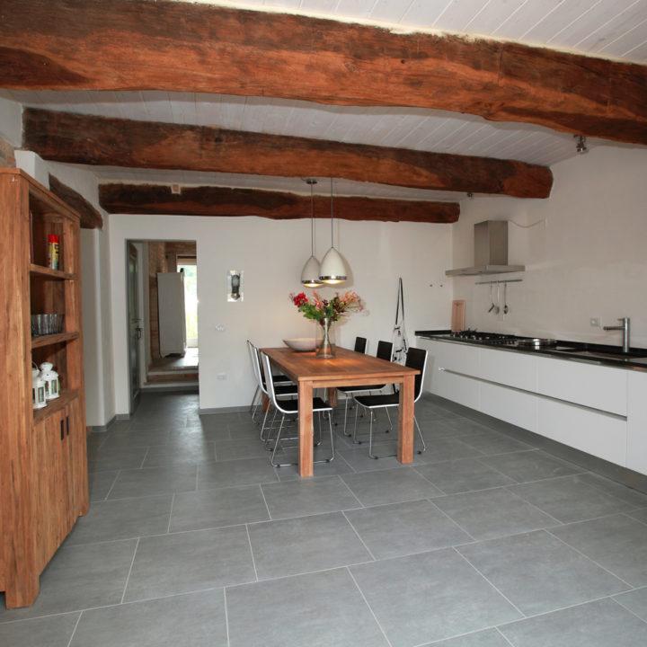 Ruime woonkamer met strakke witte keuken