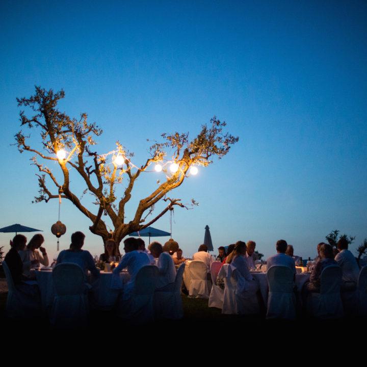 Lange tafel bij zonsondergang met boom erbij vol lampjes