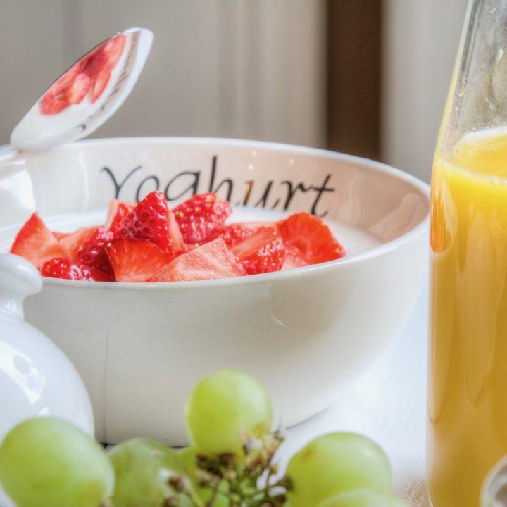 Ontbijt met yoghurt, aardebeien, sap en druiven bij de Koesfabriek in Dokkum