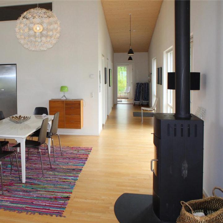 Houtkachel en eethoek met doorkijk naar slaapkamers in vakantiehuis op Funen
