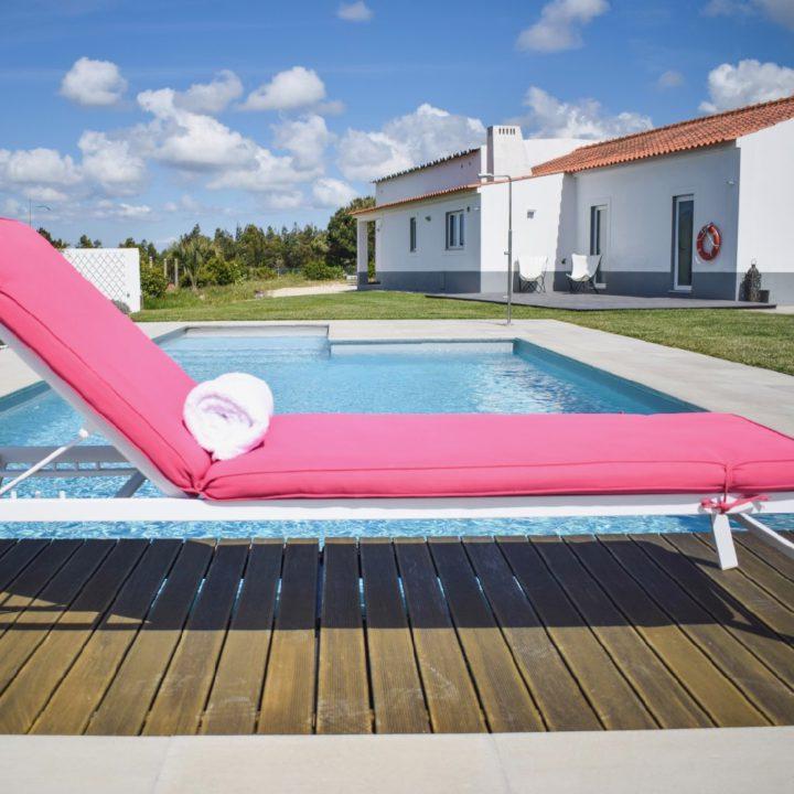 Een roze ligstoel aan de rand van het zwembad van Flamboyant B&B