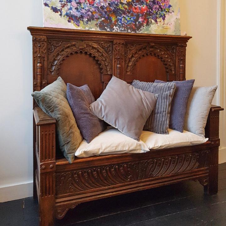 Een hoop kussens op een oncomfortabele bank in de hal van Villa Voorenburg
