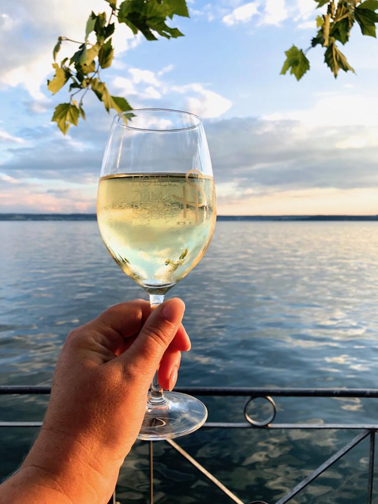 Hand houdt glas wijn vast voor een groot meer