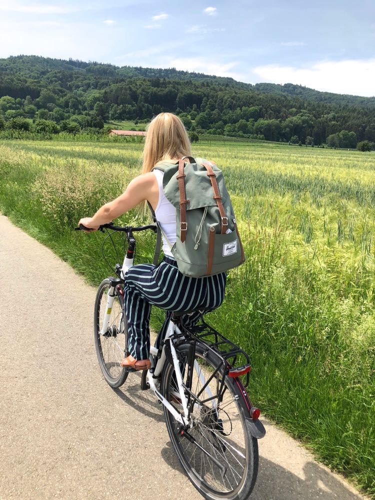 Vrouw fiets langs een grasveld