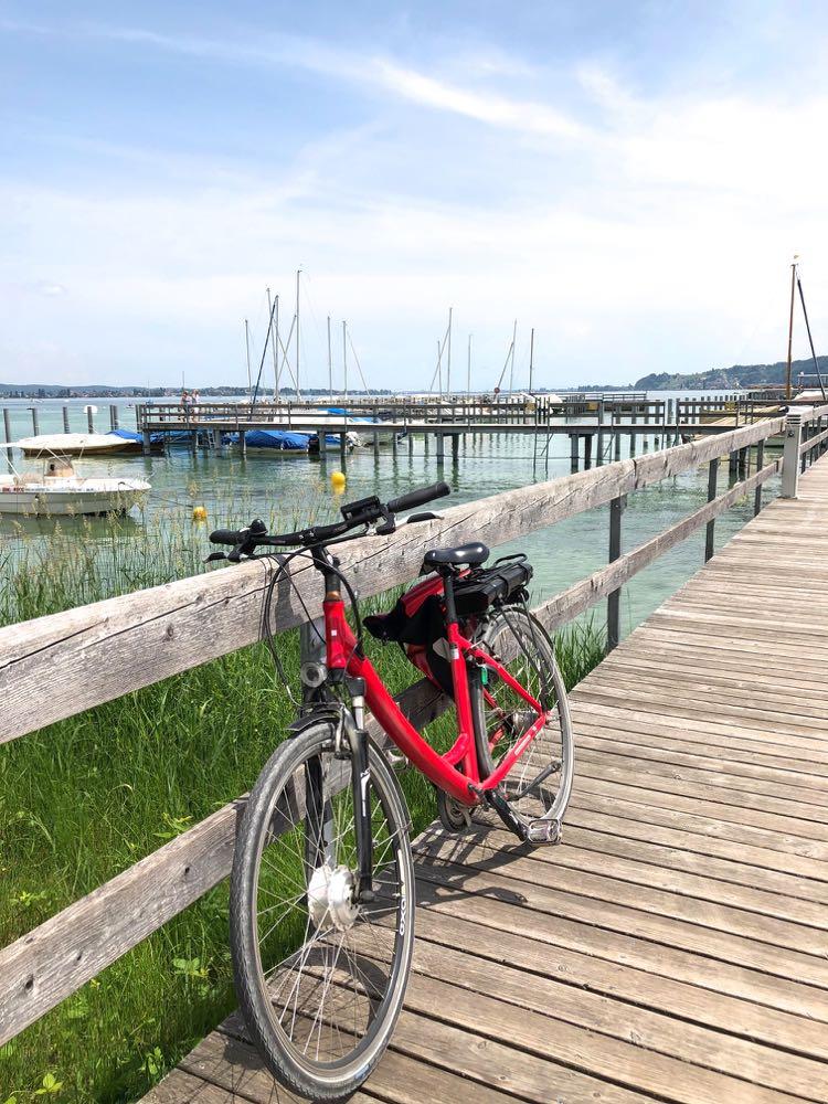 Fiets leunt tegen een houten hek bij de haven