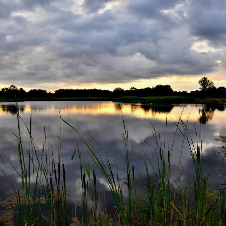 Zonsondergang met spiegeling met wolkenlucht
