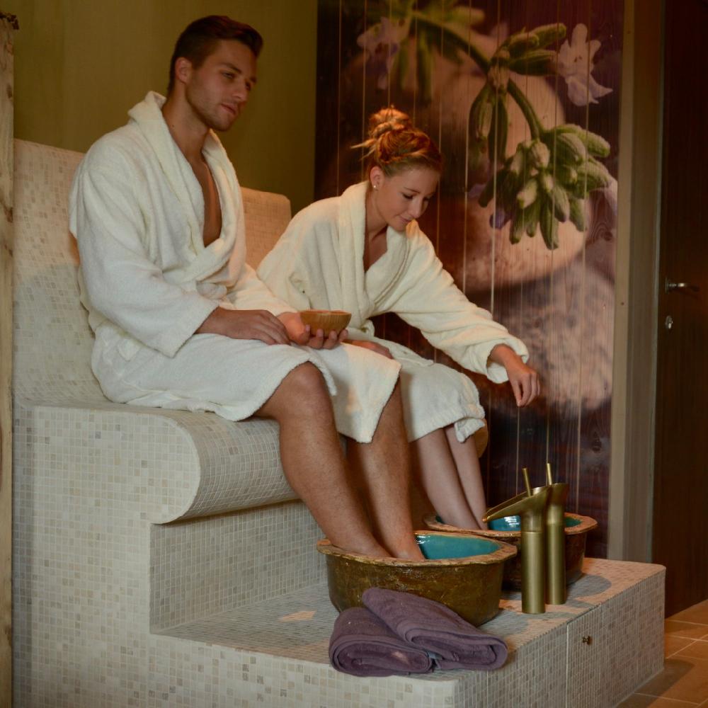 Man en vrouw genieten van hun voeten in het water