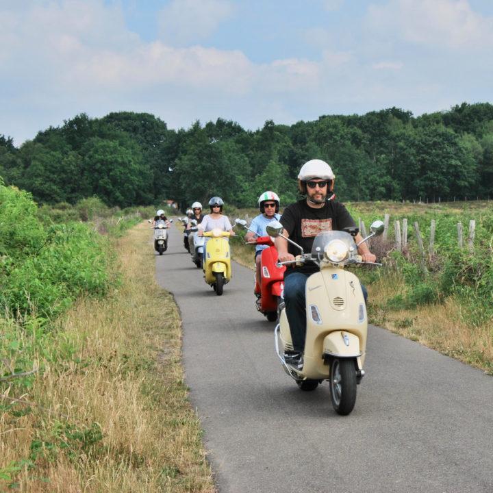 Een rij scooters op een landweg, een tof dagje uit