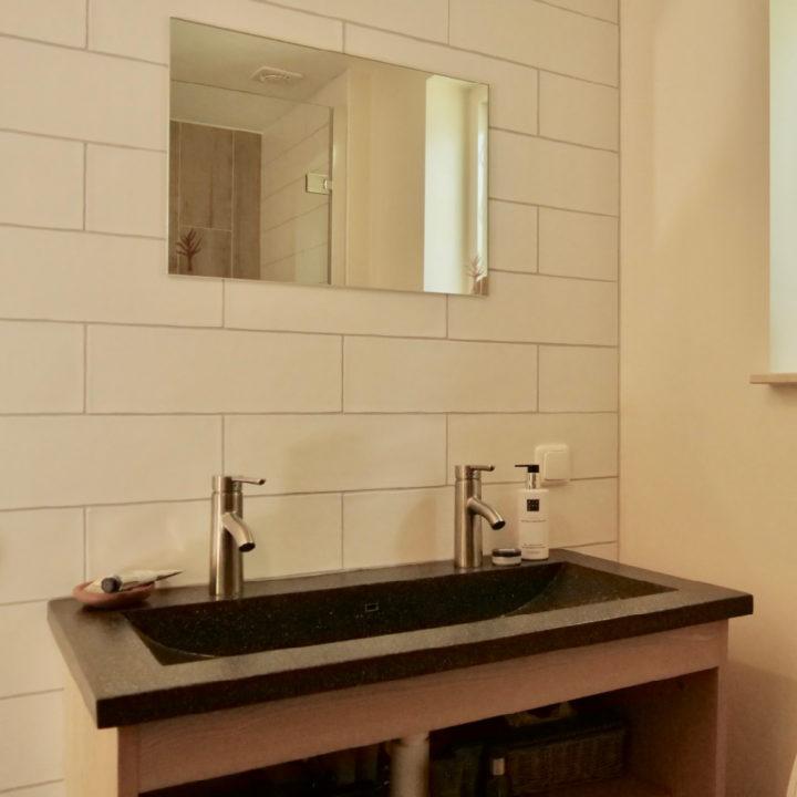 Wastafel in de badkamer met een kleine spiegel