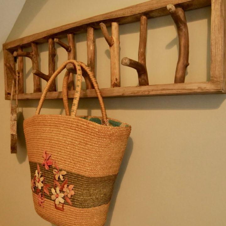 Een rieten mand hangt aan een houten rek
