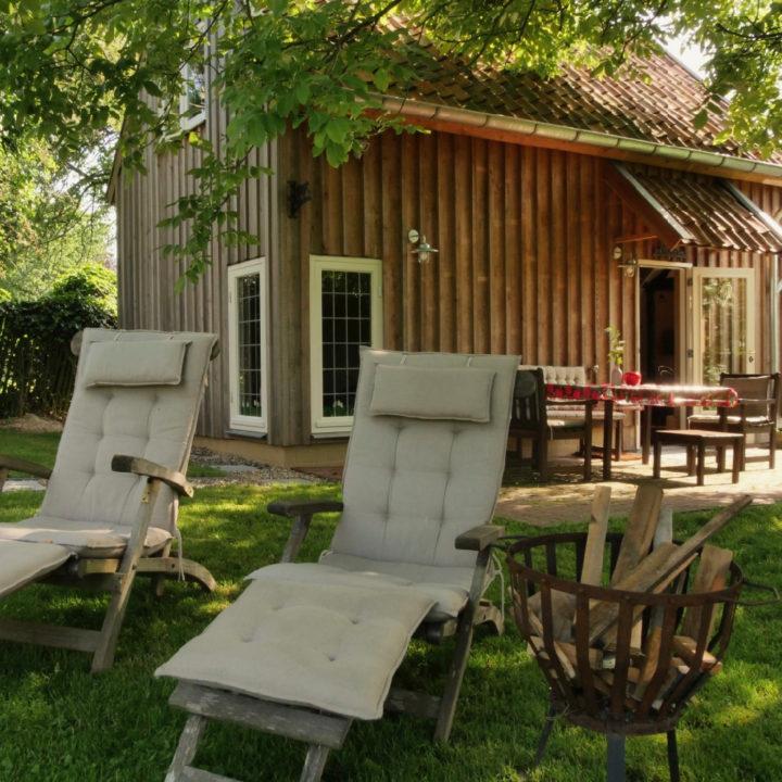 Ligstoelen voor een terrasje voor een huis in een groene omgeving