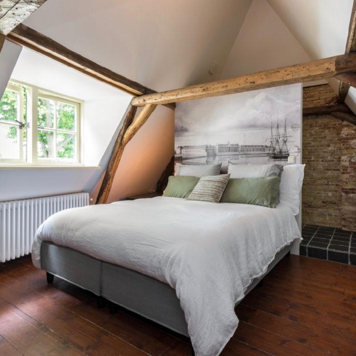 Bed in de slaapkamer met dakraam