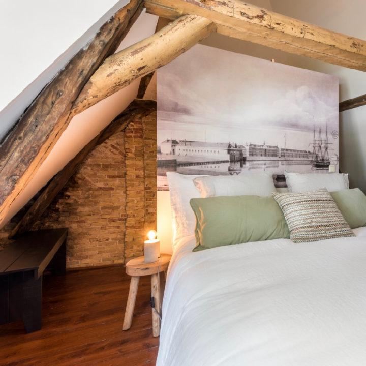 Nachtkastje met nep kaars naast bed met witte dekens en een foto van de haven op de achtergrond