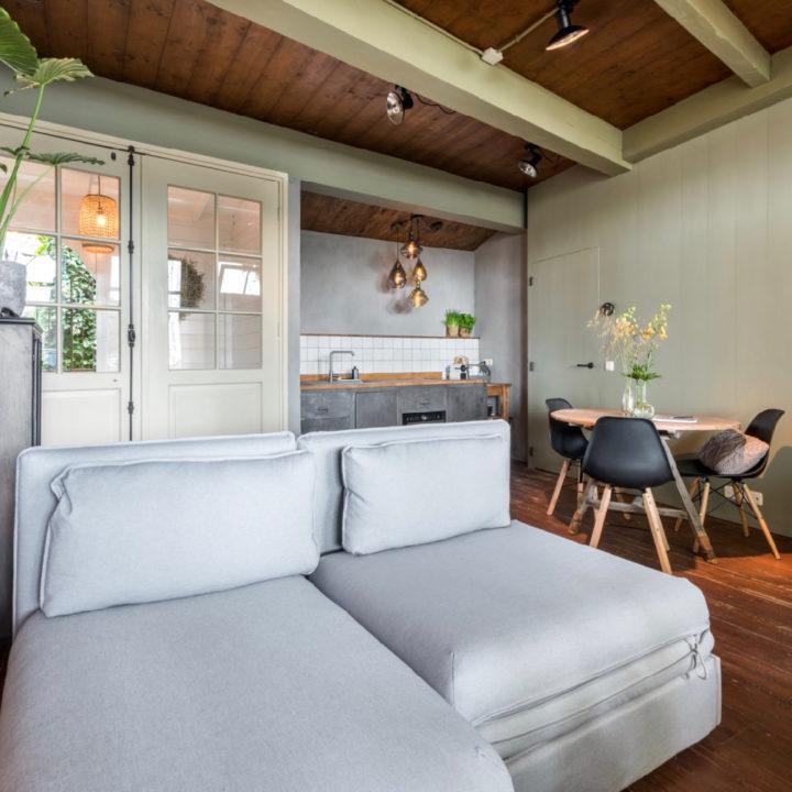 Comfortable bank in een kamer met een tafeltje en een keuken