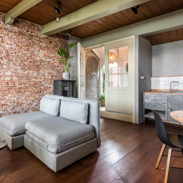De woonkamer met grijze zitbank en hoekje van de keuken bij Havenhuisje Medemblik