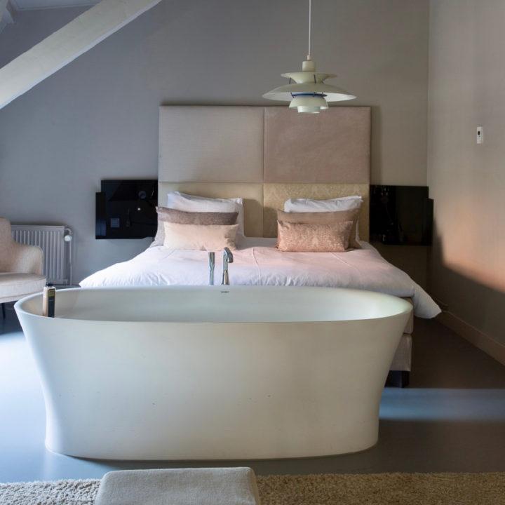 Vrijstaand ovaal bad midden in slaapkamer