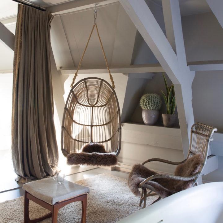 Hangstoel en rotan stoel in een van de suites