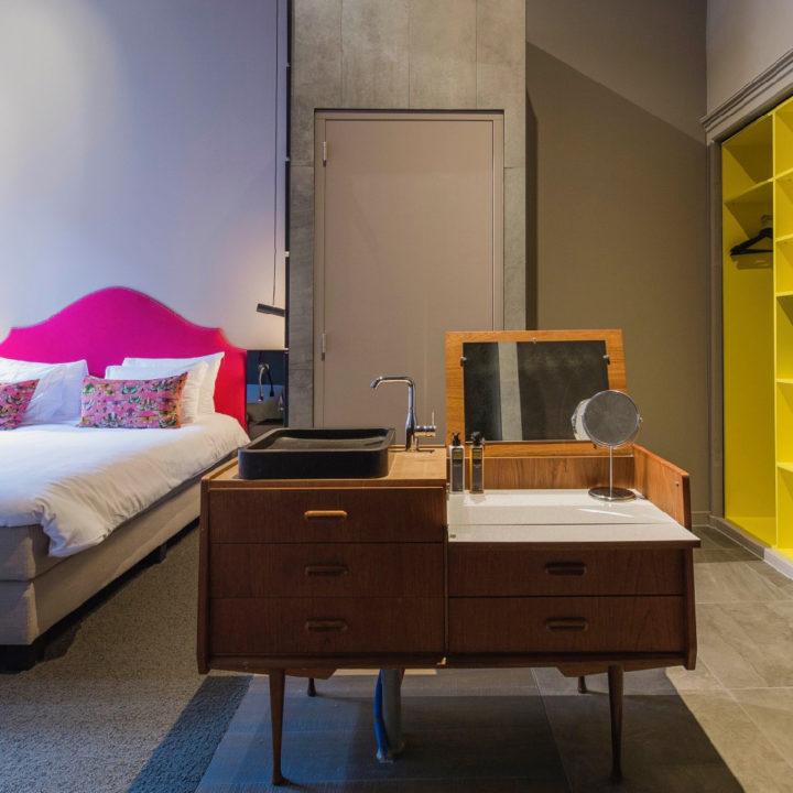 Hippe hotelkamer met geel, roze en antiek badmeubel midden in de kamer