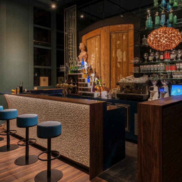 Bar met blauwe krukken, flessen tegen achterwand