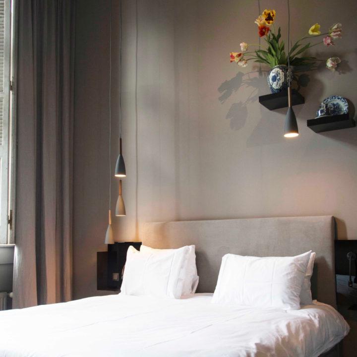 Wit opgemaakt bed, grijze achterwand, plankjes met bloemen