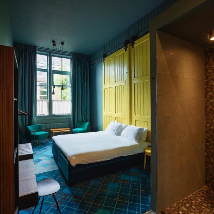 Tweepersoons hotelkamer met blauw, groen en gele tinten