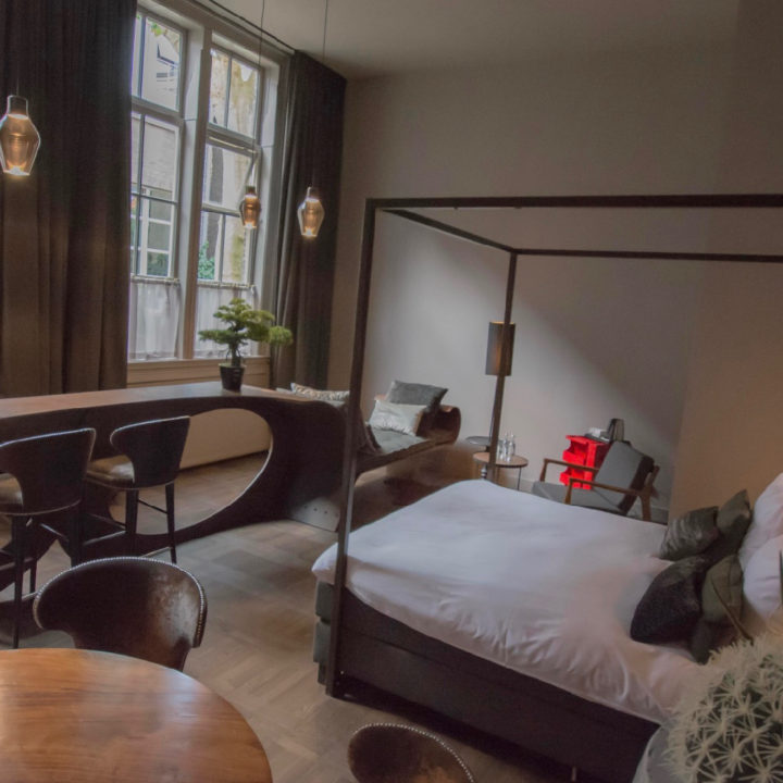 Ruime hotelkamer met tafel met twee stoelen, hemelbed