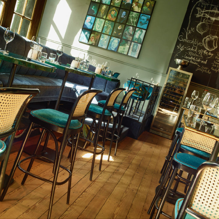 Groene muur, hoge tafels met groene barkrukken en blauwe bank