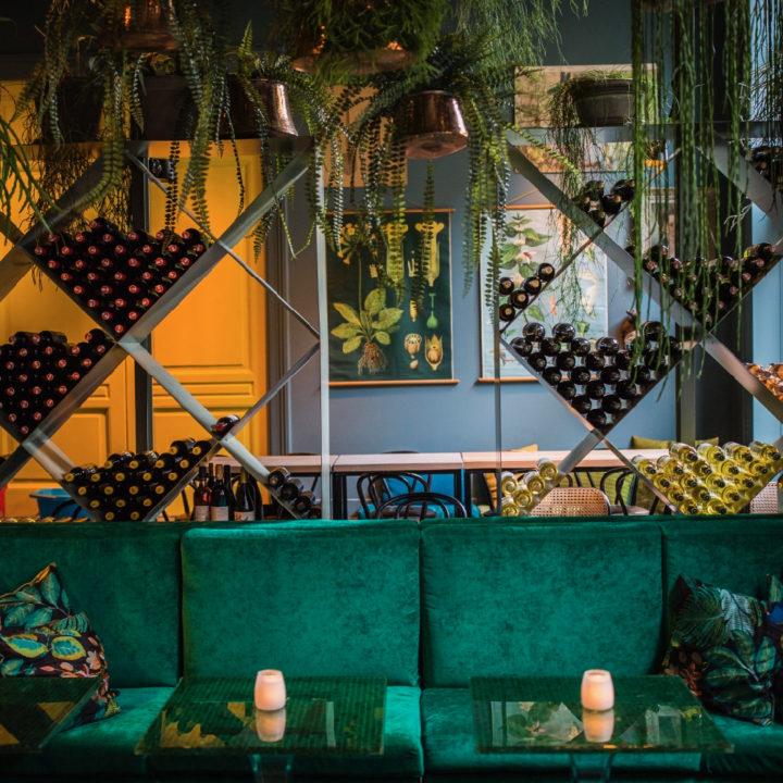 Groene fluwelen bank met wijnrekken erachter