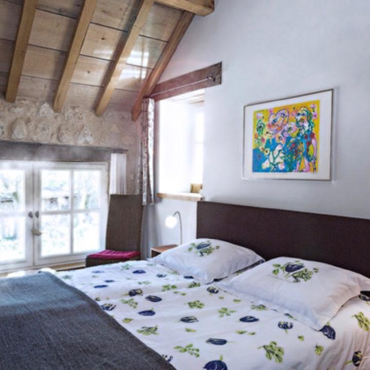 Tweepersoons bed in slaapkamer met schuine wand