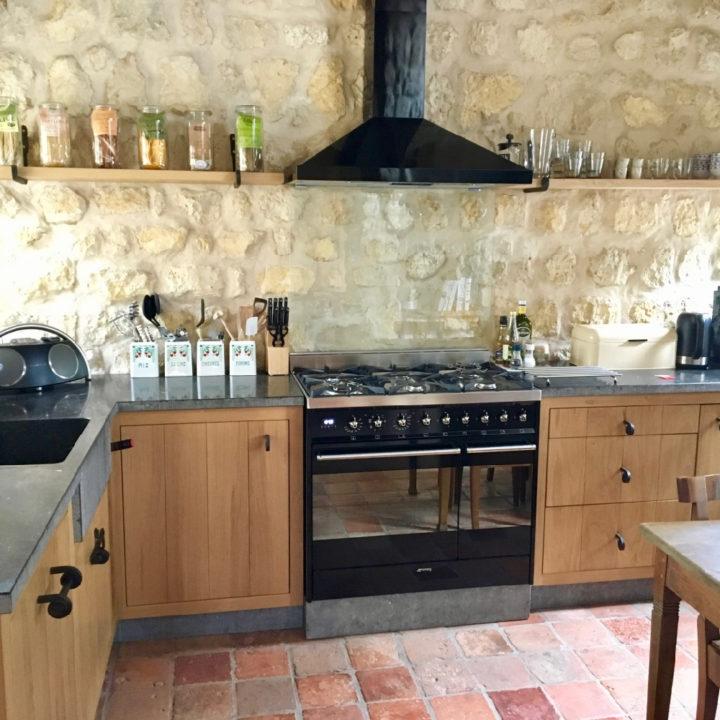 Houten keuken met natuurstenen blad, rode estrikken op de grond