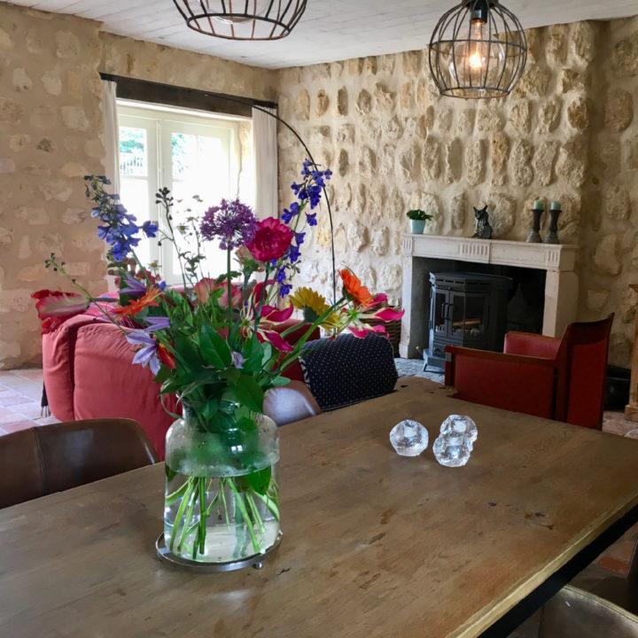 Bloemen op eettafel en zithoek met haard