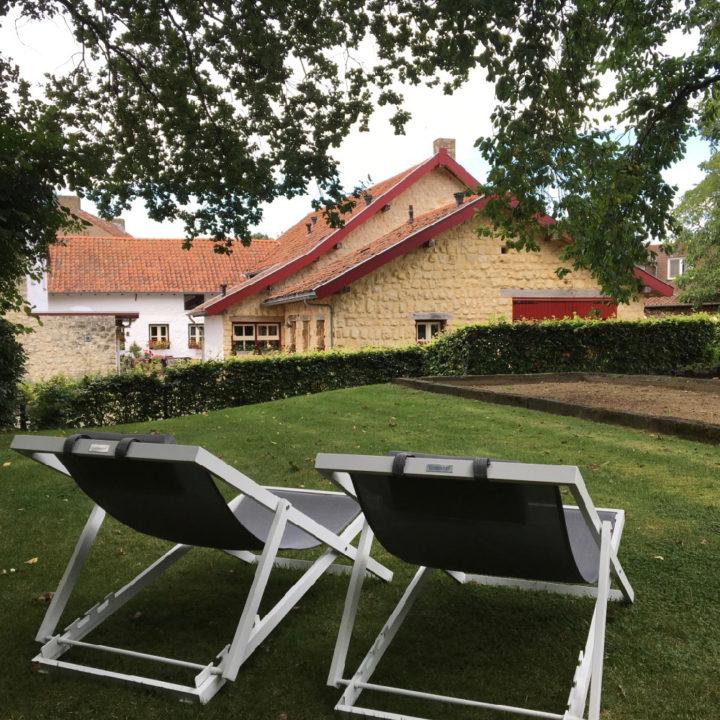 Ligstoelen in het gras bij vakantiehuis