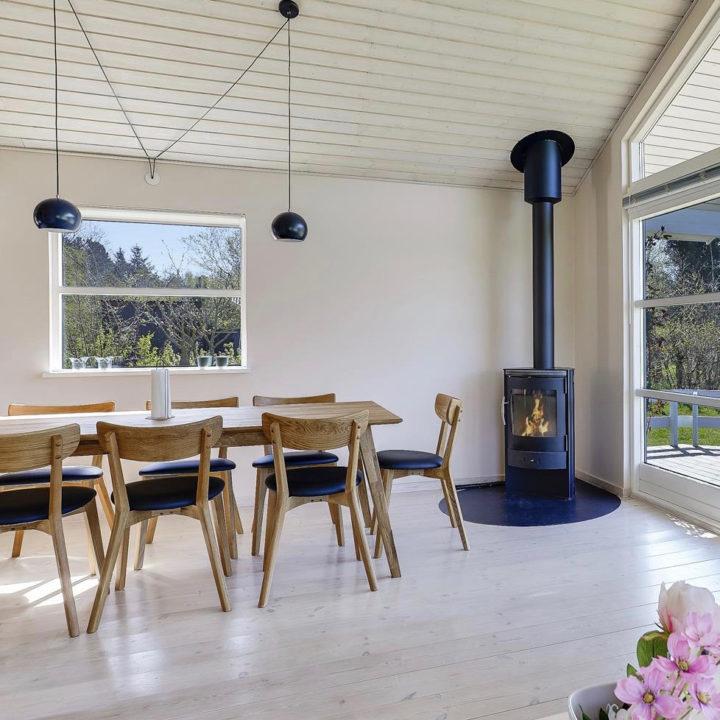 Zwarte houtkachel voor het raam, houten eettafel op witte houten vloer