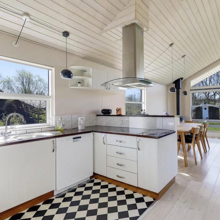 Open witte keuken met eettafel met houten stoelen