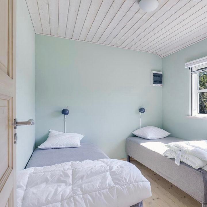 Slaapkamer met mintgroene muren en twee losse bedden