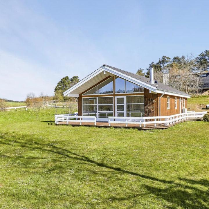 Houten vakantiehuis in grasveld met grote glazen gevel