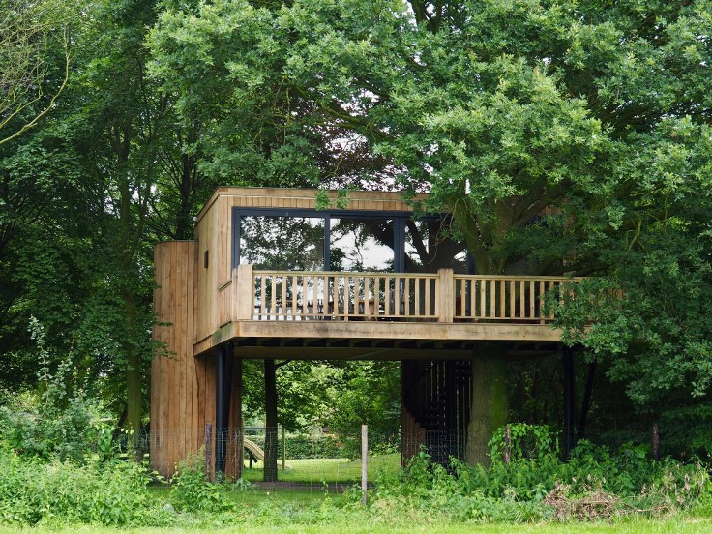 Design boomhut omringd door groen
