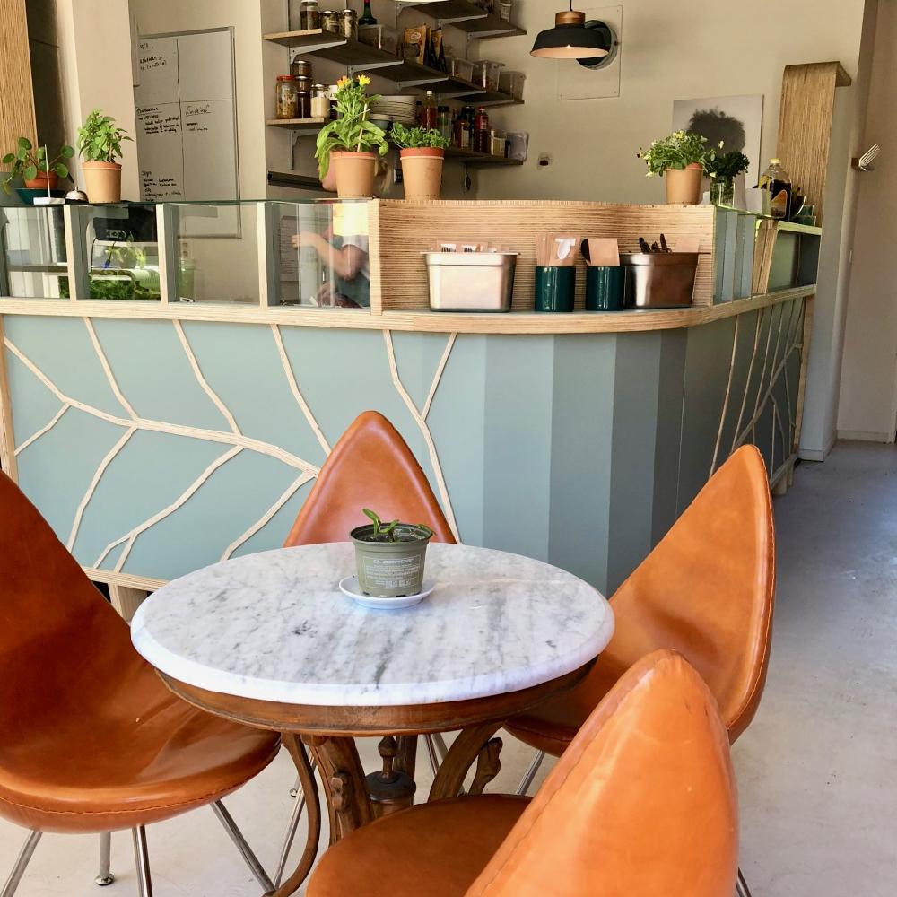 Tafel en stoelen met balie bij Stroom