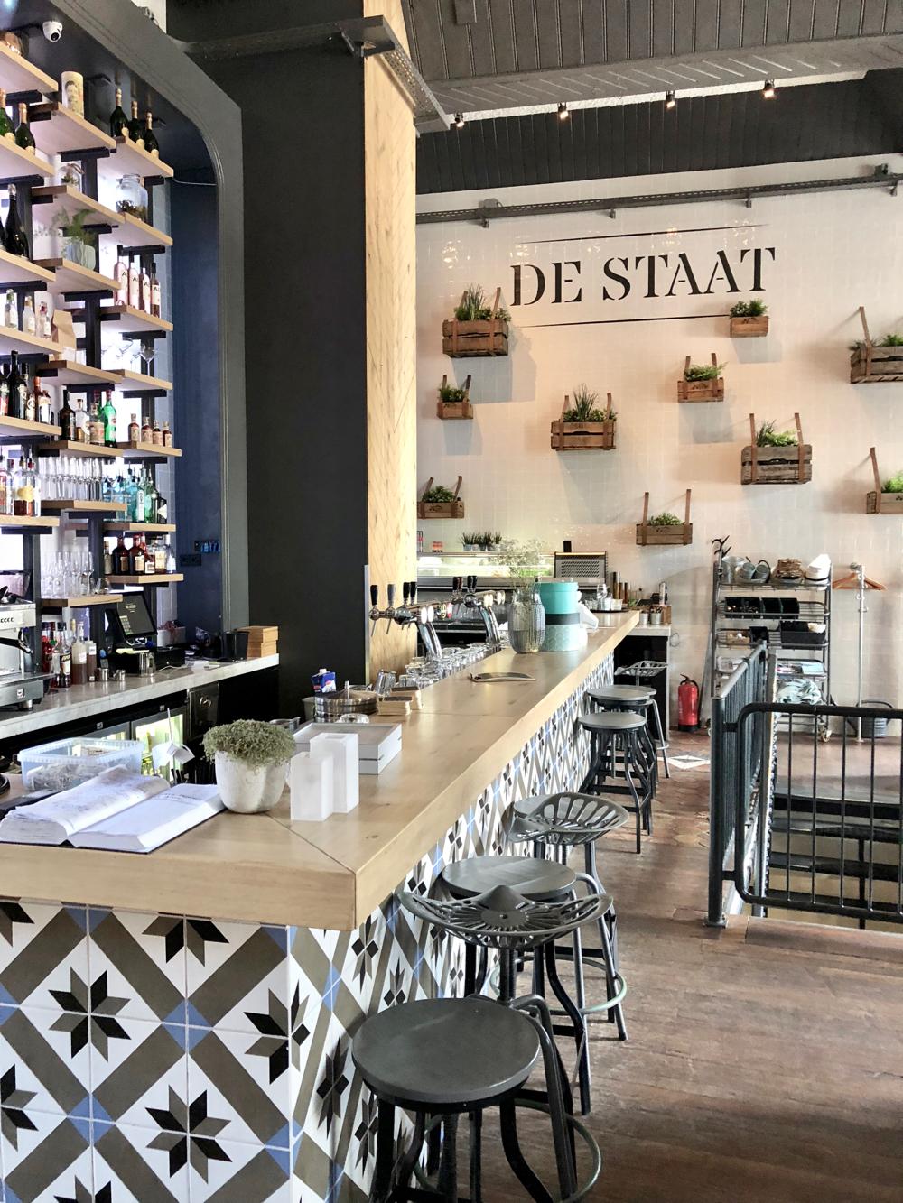 Bar met barkrukken en hoge wand met tegels bij De STAAT