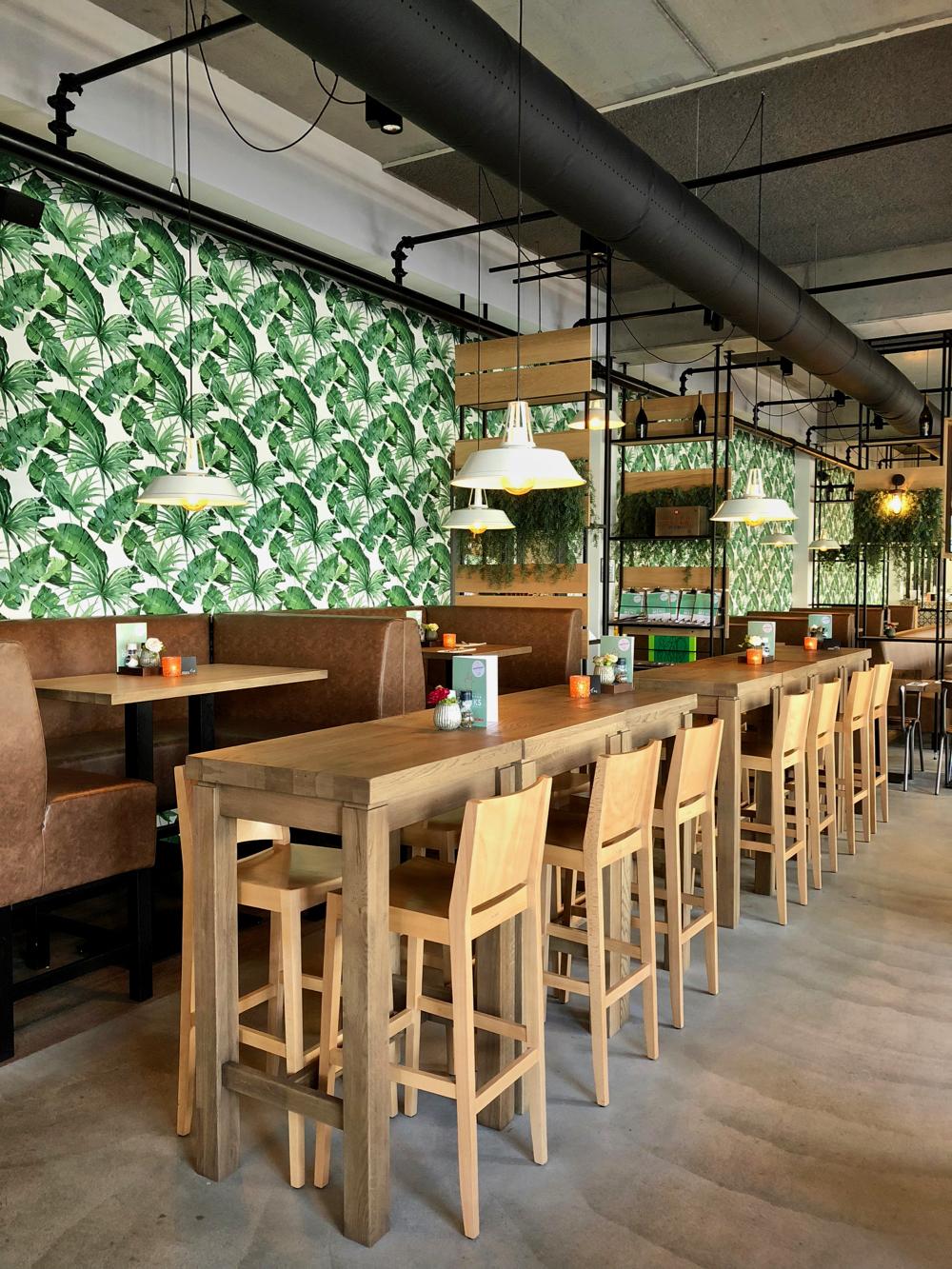 Hoge tafels en een jungle behang in het restaurant