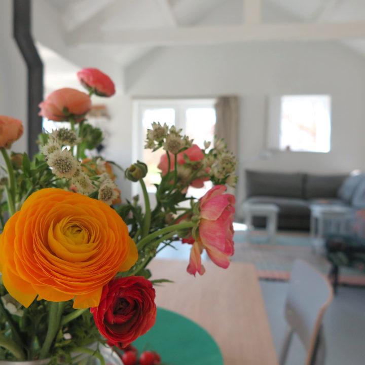 Bloemen op de eettafel en doorkijkje naar de zithoek