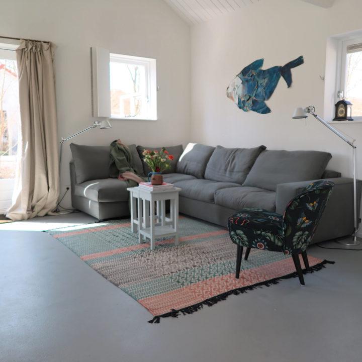 Zithoek met grijze bank en gekleurde fauteuil