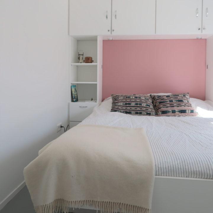 Tweepersoons bed met roze achterwand met kasten