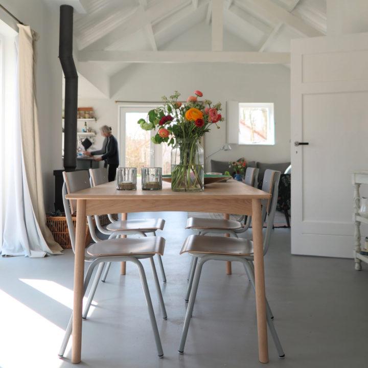 Doorkijkje vanaf de eettafel richting de houtkachel, keuken en zithoek