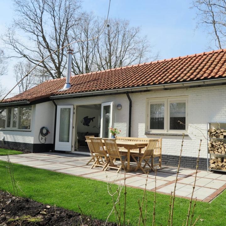 Wit vakantiehuisje met terras ervoor