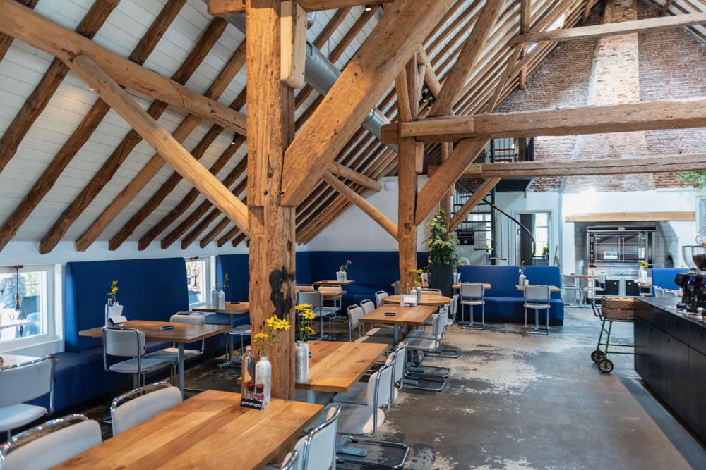 Interieur restaurant Vroeg met houten tafels, gebinten, witte stoelen