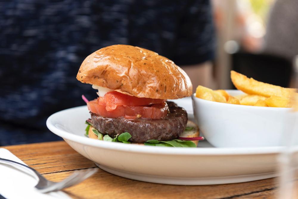 Hamburger op een wit bord met friet in een wit schaaltje